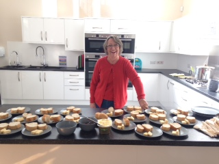 Picture of Teresa In Assumption Church Hall Kitchen with plats of bread at the ready